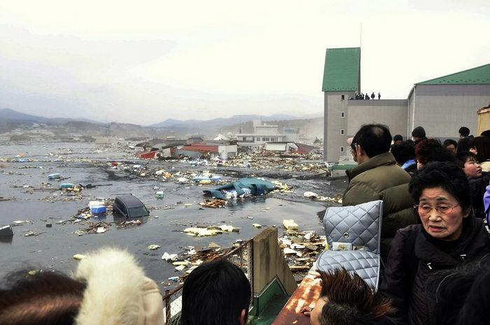 Люди наблюдают последствия волн цунами, обрушившихся на порт Кесеннума, северная Япония, после сильнейшего землетрясения, охватившего эту местность (AP Photo/Keichi Nakane, The Yomiuri Shimbun).
