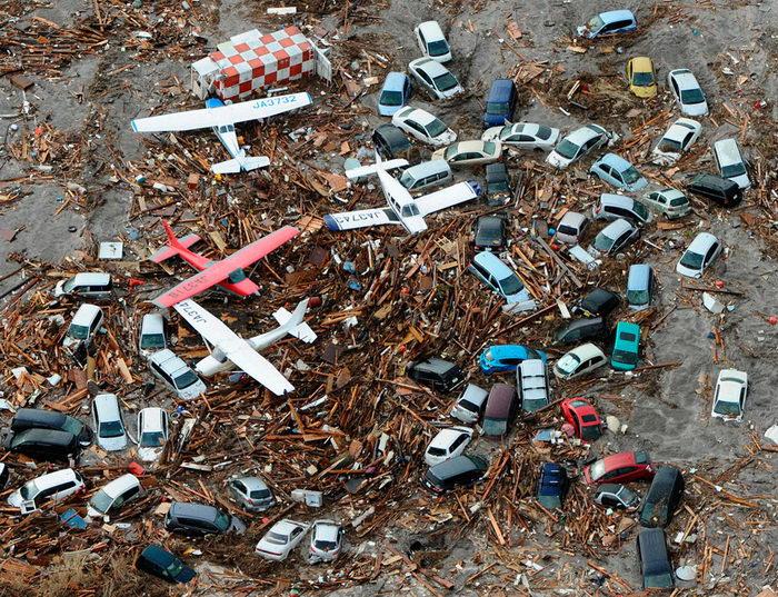 Машины и самолёты, сметённые цунами, запечатлены среди развалин аэропорта Сендай, северо-восточная Япония. После землетрясения было несколько сильных толчков и последовало 10-метровое цунами, что также стало причиной сильных колебаний сооружений в Токио (REUTERS/KYODO).