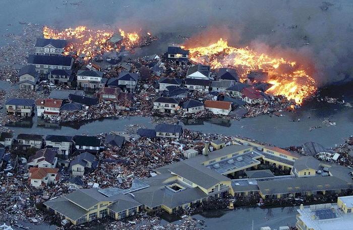 Дома, прижатые друг к другу и охваченные пламенем. Одновременно территория затоплена разливом реки Натори, в устье которой у одноимённого города ударили чередующиеся волны цунами (AP Photo/Yasushi Kanno, The Yomiuri Shimbun).