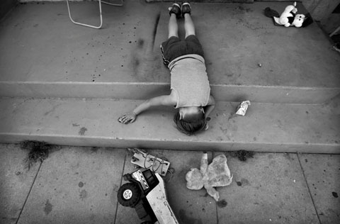 Barbara Davidson/The Los Angeles Times/ Первое место, «Тематический фоторепортаж» (подразделение газеты): Жосуэ играет на крыльце. Его мать рассказывает, как оживленное общение мальчика с братьями и сестрами прекратилось в миг, когда он был застрелен.