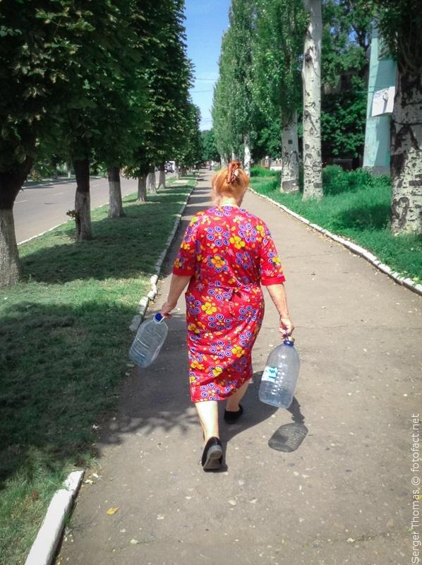 Бабушка с пустыми баками для воды